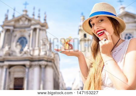 Young woman holding italian chocolate with bow on Turin city background. Turin in Piedmont region in Italy is famous of its chocolate making