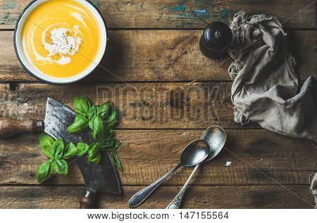 Pumpkin cream soup in bowl with fresh basil and spices over old rustic wooden background, top view, copy space, horizontall composition