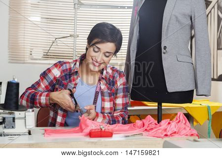 Tailor Cutting Fabric At Workbench By Mannequin