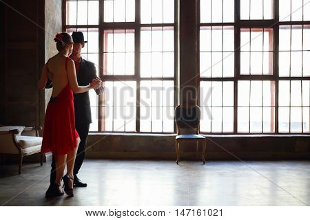 Woman in red dress and man in black suit dance tango near window