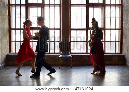 Girl plays sax and beautiful couple dance tango near big window
