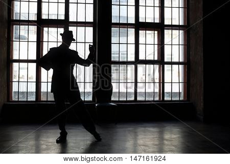 Silhouette of man in black suit and hat dancing tango in room with big window