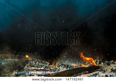 Fire showing piled logs burning in a fire place.