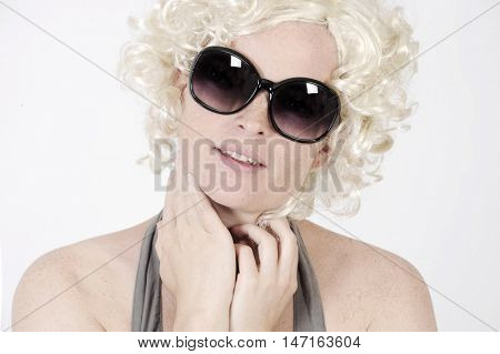 Beautiful young woman is wearing sunglasses and a blonde wig in Marylin style. Studio shot with light background. Isolated.