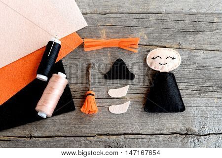How to sew a Halloween witch doll. Step. Halloween witch ornament details, scissors, thread, needle, felt sheets set on wooden background. Handmade crafts for children and beginners. Top view