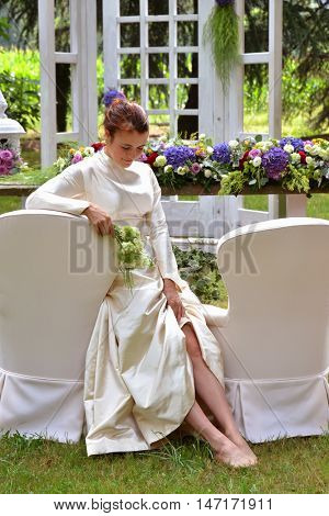 Outdoor sad bride after being stood up on her wedding day waiting her husband.