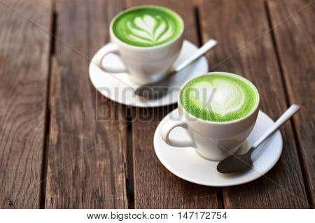 Two cups of matcha latte with latte art on wooden table.
