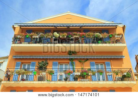 Beautiful Facade Of House In Provence, Orange Yellow With Blue Shutters, Numerous Green Plants In Tu