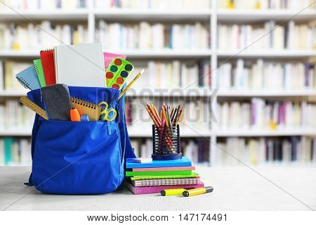 Blue backpack with school supplies on wooden table against blurred book shelves. School concept.