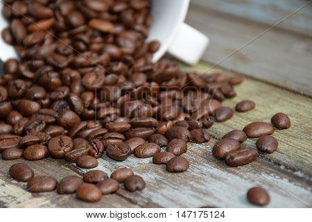 Kaffekop som ligger ned med kaffebønner som er røget ud