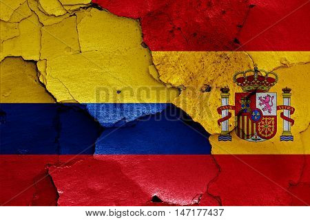 flags of Colombia and Spain painted on cracked wall