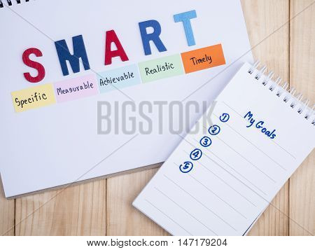 Word spell SMART Goals and handwriting my goal in notebook on wood background (Business Concept)