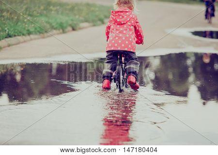 little girl riding bike in water puddle, kids seasonal activities