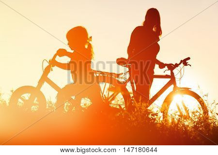 mother and little daughter riding bikes at sunset, active family