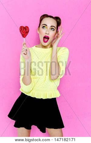 Beauty fashion model girl Eating colourful heart-shaped lollipop. heart-shaped Lollypop. Surprised Young funny woman with  hairstyle, pink makeup isolated on white background