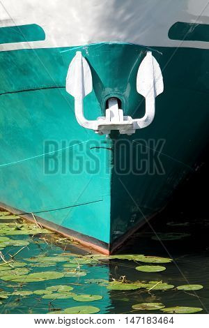 Cyan bow of the ship with white anchor. Light spots and water lily.