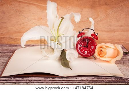 lilly flower and watch on note book wooden background
