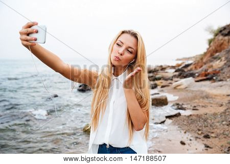 Young smiling beautiful woman sending air kiss and making selfie while standing on the rocky beach