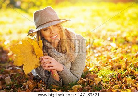 Closeup portrait of beautiful happy young blonde Caucasian woman in gray sweater, floppy hat and scarf, in park in autumn holding leaves, lying in leaves. Natural light, retouched, vibrant colors.