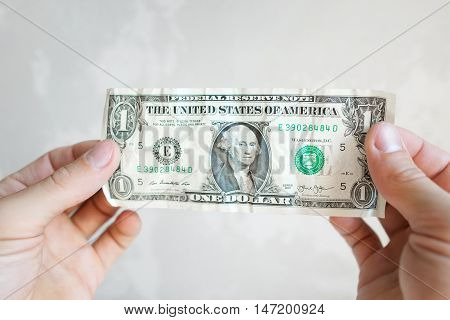 UKRAINE, KHARKIV- SEPTEMBER 4 , 2016. One american dollar banknote in male hands. Old crumpled buck bill close-up on white background, copy space