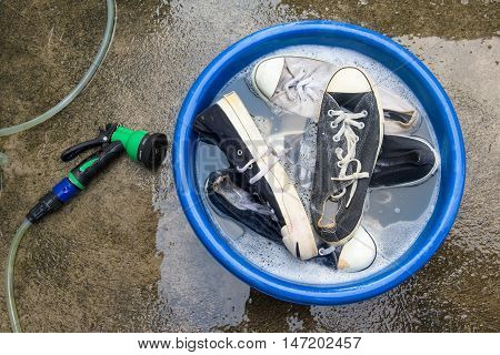 Shoes or sneakers in wash bucket with soapy water and water hose