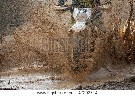 Motocross driver splashing mud on wet and muddy terrain