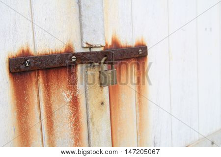Old lock and rusty iron hasp on a white wooden door with rust stains running down the door.