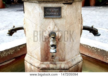 Old water fountain with gargoyle heads sign reads
