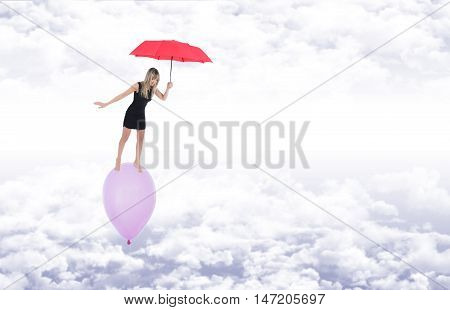 Barefoot girl over a balloon she keeps in balance with a red umbrella while flying over white clouds in a blue sky