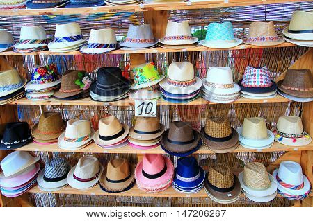 Rows of multi-colored straw panama hats for sale on shelves in a market stall