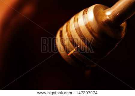 Honey stick with flowing honey over black background close up