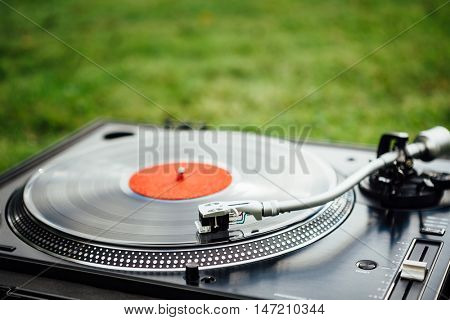 vinyl disc playing on turntable, green grass background