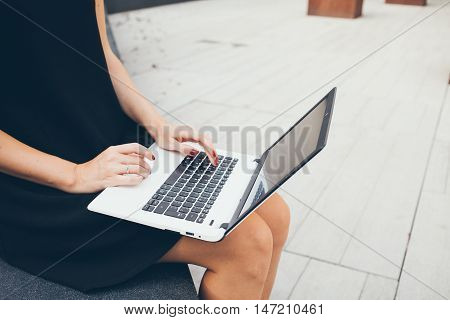 Cropped shot of beautiful young female using portable laptop computer while sitting in a backyard of office building. Looking up for information on the internet reading news,surfing online shops, browsing social network pages