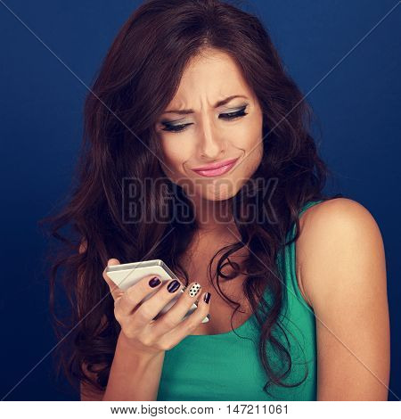 Cranky surprisung grimacing young woman reading sms on mobile phone holding it in hand on blue background. Toned portrait poster