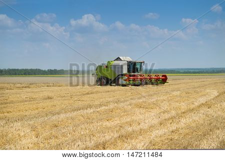 KRASNODAR REGION, RUSSIA - JUL 7, 2015: Green harvester on yellow wheat field, In 2015 in Krasnodar region have collected record grain harvest - 102 million tons of grain
