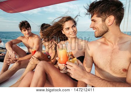 Group of young happy friends drinking and having party on a sailing boat