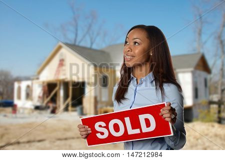 African American Real Estate Agent holding a sold sign with house in the background