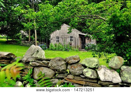 Jamestown Rhode Island - July 18 2015: Wooden Caretaker's Cottage with stone wall at historic 1796 Watson Farm on Conanicut Island *