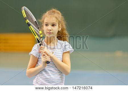half portrait of young girl tennis player holding her racket
