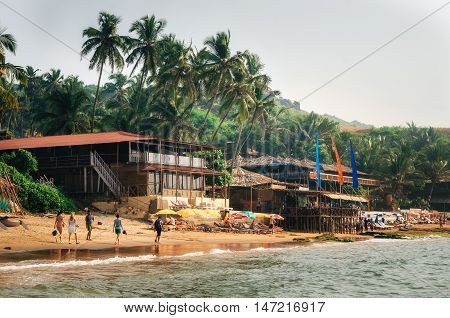 Chapora Goa India - Dec 9 2014: Bungalow traditional boat and restaurant shacks on piles at the beach of Anjuna North Goa India