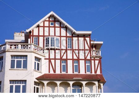Historical architecture in De Haan Belgium in Belle Epoque style with an interesting red roofed townhouse against a blue sky