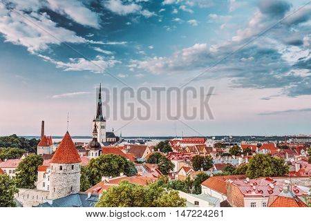 Evening Tallinn's Old Town Cityscape At Sunset, Clear Blue Sky In Estonia. One Can See The Spiers Of St. Nicholas Church And Towers, Surrounded By A Park.