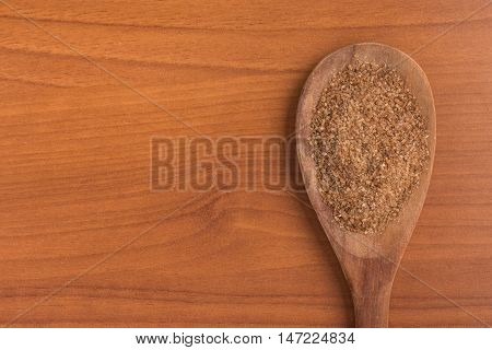 Ground Wheat into a spoon over a wooden table. Trigo para quibe. Kibbeh
