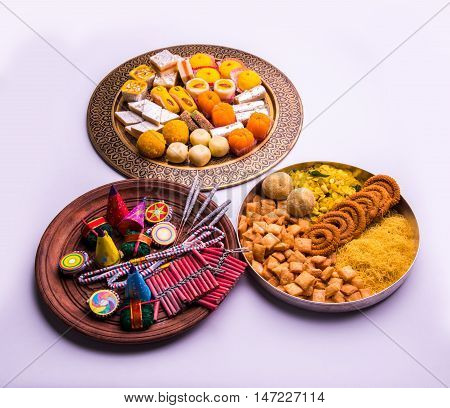 indian sweet food served with assorted fire crackers in separate plate showing diwali concept poster