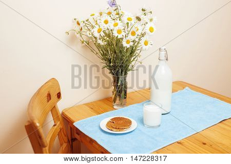 Simply stylish wooden kitchen with bottle of milk and glass on table, summer flowers camomile, healthy foog moring concept country interior