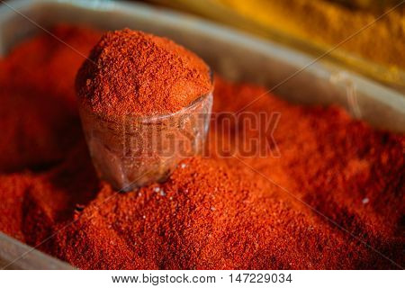 Close View Of Glass With Powdered Paprika Or Cayenne Pepper, Standing In The Heap Of Bright Red Fragrant Spice On Sale At The East Market, Bazaar.