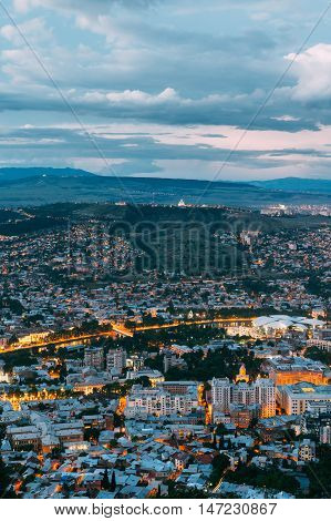Tbilisi, Georgia. The Aerial Cityscape View Of Capital In Evening Illimination, The Modern City District Of High-Rise Buildings Foreground. Dramatic Blue Cloudy Sky Of Sunset Sunrise Over Hilly Area.