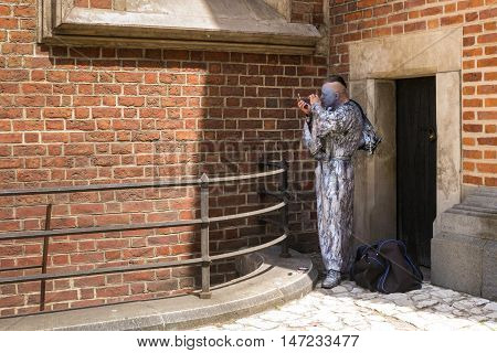POLAND, KRAKOW - MAY 27, 2016: Unknown actor playing the role of a living monument to preparing for his presentation. The walls of the famous St Mary's church in Krakow.