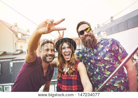 Man makes peace sign beside two smiling friends while they take photo on their apartment patio