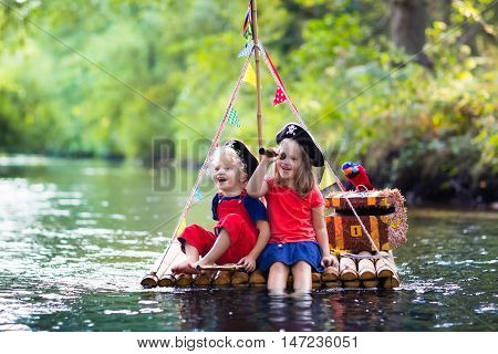 Kids dressed in pirate costumes and hats with treasure chest spyglasses and swords playing on wooden raft sailing in a river on hot summer day. Pirates role game for children. Water fun for family.
